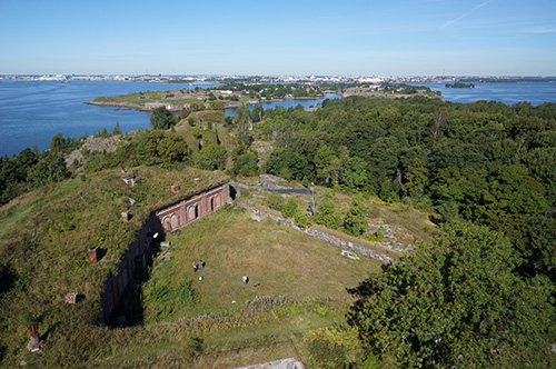 Tiilestä muurattu rakennus vallituksen alla, saaria ja kauempana mantereen rakennuksia.
