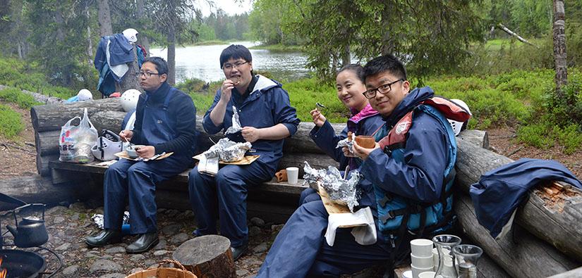 Neljä henkilöä syö sadevaatteet päällä eväitä taukopaikalla.