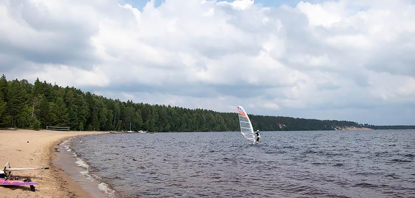 Leijasurfaaja järvellä lähellä hiekkarantaa. Rannalla on toinen surffilauta ja kauempana veneitä laiturissa.