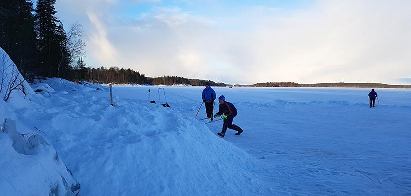 Kolme vapaaehtoista kolaa lunta apukinokseksi rannan lähelle.