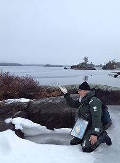 Mies on kontallaan jäällä tutkimassa keväällä romahtanutta norpan pesää.