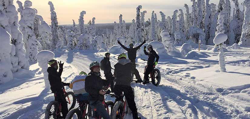 Seitsemän pyöräilijää on pysähtynyt polulle talviseen metsään. Ympärillä on tykkylumen peitossa olevia kuusia.