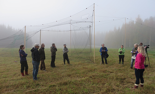 Tiedotusvälineet tutustuvat uudenmalliseen rysään, joka on levitetty näytille pellolle.