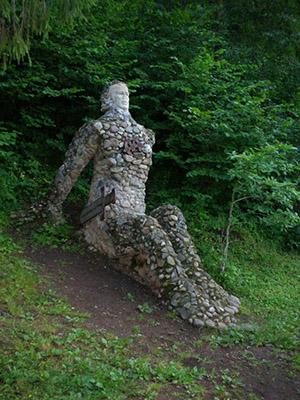 Pikkukivistä rakennettu ihmishamo istuu maassa ja näyttää sulautuvan maahan. Taustalla on puista ja pensaita.