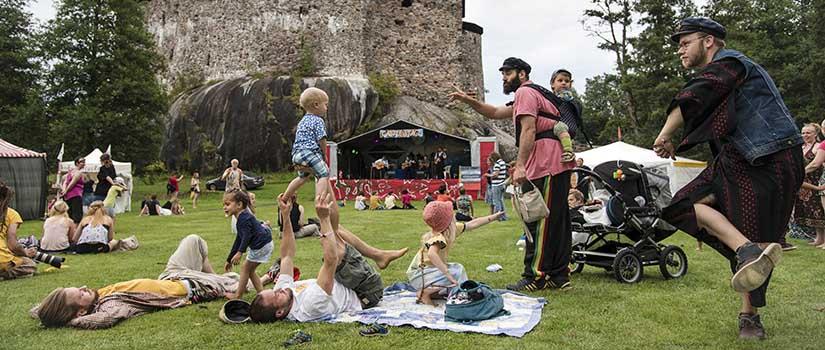 Soittolava Raaseporin linnan edustan nurmikolla. Paljon eri-ikäisiä katsojia istuu ja seisoo nurmikolla.