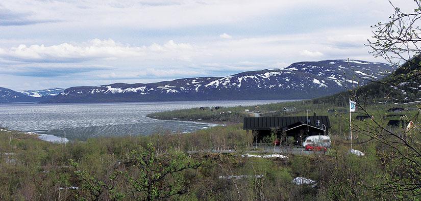 Järven rannalla on rakennuksia ja lipputanko. Kauempana on tuntureita, joiden rinteillä on laikuttain lunta.