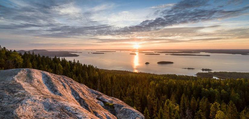 Vaaran laelta avautuva järvimaisema. Aurinko on juuri noussut horisontin takaa.