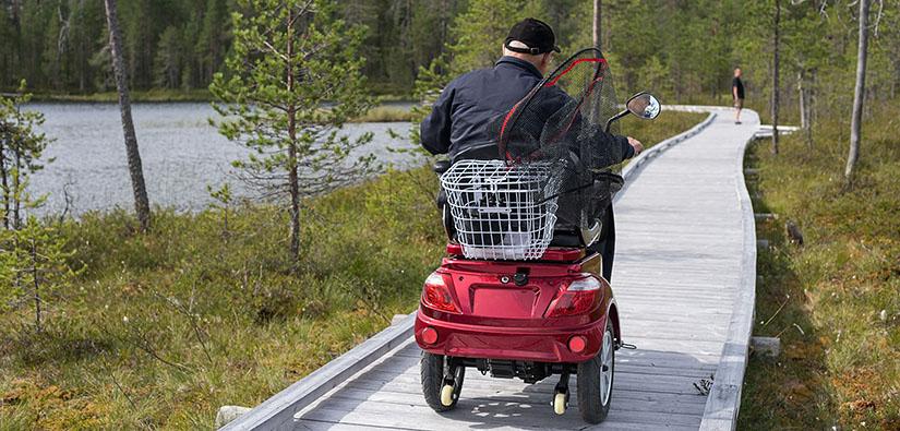 Mies ajaa sähköisellä pyörätuolilla pitkospuita pitkin. Mopon kyydissä on kalahaavi.