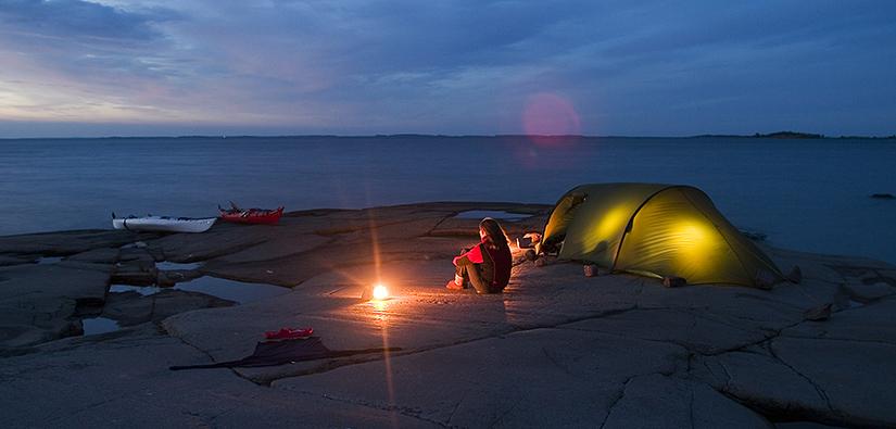 Meren ympäröimällä kalliorannalla on kaksi kanoottia ja teltta. Ihminen istuu kalliolla iltahämärässä taskunlampun valossa.