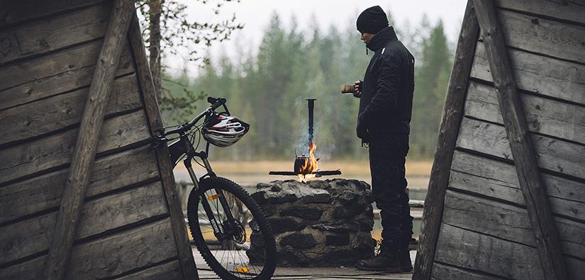 Mies seisoo kuksa kädessä kivistä muuratun tulipaikan vieressä. Polkupyörä nojaa laavuun.