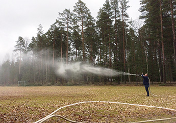 Mies seisoo tyhjällä pelikentällä ja suihkuttaa vettä vesiletkusta.