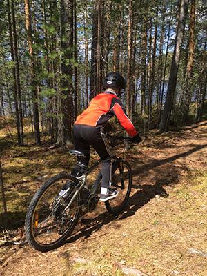 Poika ajaa polkupyörällä polkua pitkin. Puiden takaa näkyy järvi.