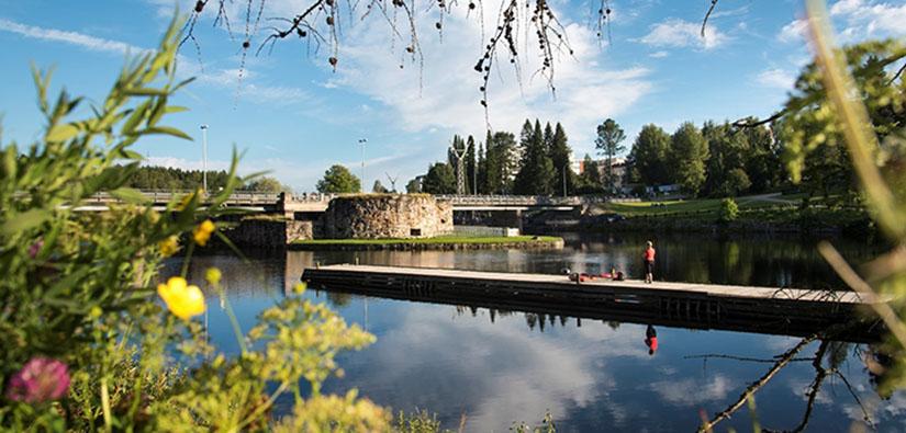 Tyyni järven pinta, pitkä laituri sekä linnanrauniot, joiden takana kulkee silta.
