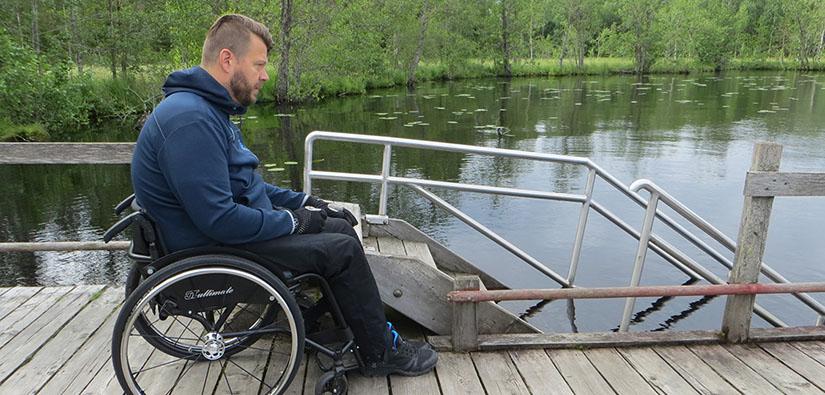 Mies istuu pyörätuolissa laiturilla.