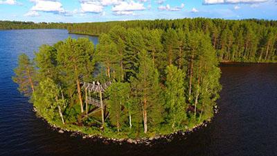 Pieni saari, jossa on näkötorni. Taustalla järvi ja metsää.