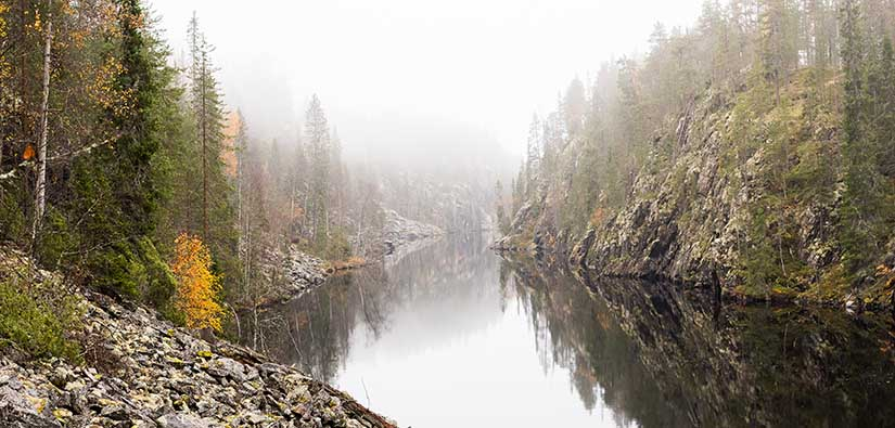 Kapea vesiväylä kulkee korkeiden jäkälää kasvavien kallioiden välissä.