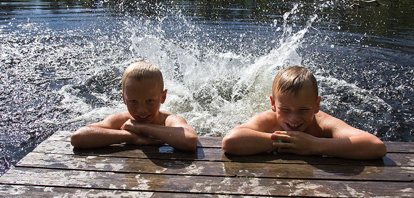 Kaksi poikaa on laiturin päässä vedessä kyynärpäät ristissä ja polskii jaloilla vettä.