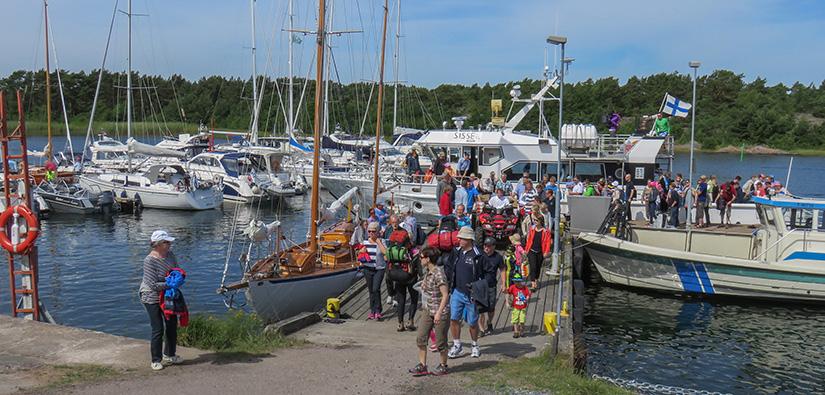 Ihmisiä tulossa betonilaituria pitkin rantaan Örön vierasvenesatamassa, taustalla purje- ja moottoriveneitä.