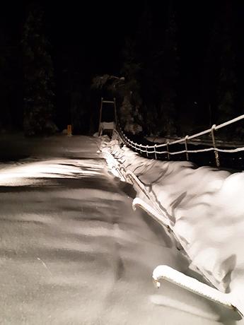 Runsaan lumen peittämä toiselta puolelta romahtanut riippusilta.