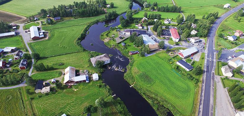 Ilmakuva. Joki virtaa peltojen keskellä. Joen molemmilla rannoilla on taloja ja maatalousrakennuksia sekä pieniä metsiköitä.