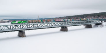 An extra long train (LHT) crosses the Ounasjoki River along the railway bridge.