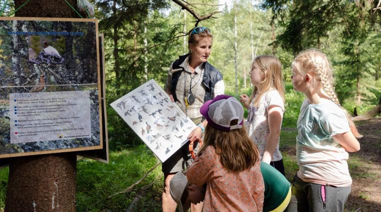 Lapset katsovat lajintunnistustaulua eräkummin ohjauksessa.