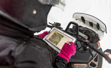 Woman looking at GPS device while sitting on a snowmobile.