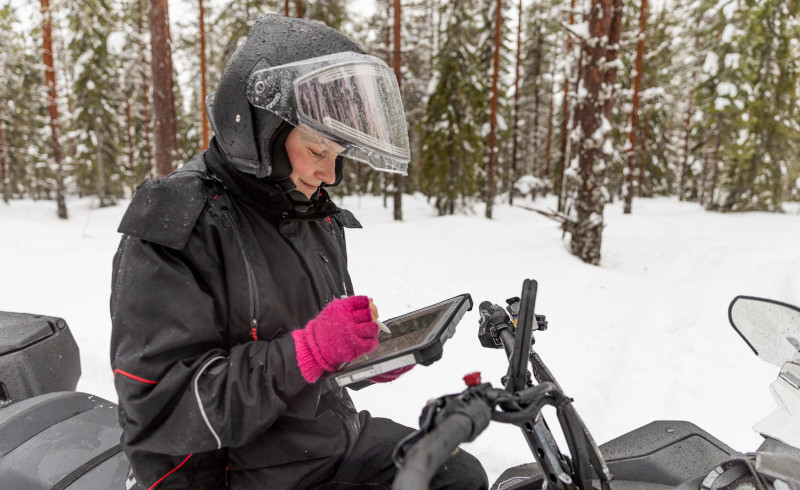 A woman sits on a snowmobile and examines a GPS device.
