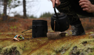 A hiker is pouring coffee brewed over a campfire into a wooden cup.