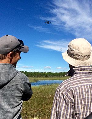 Kaksi miestä katsoo, kun drone lentää suon yläpuolella.