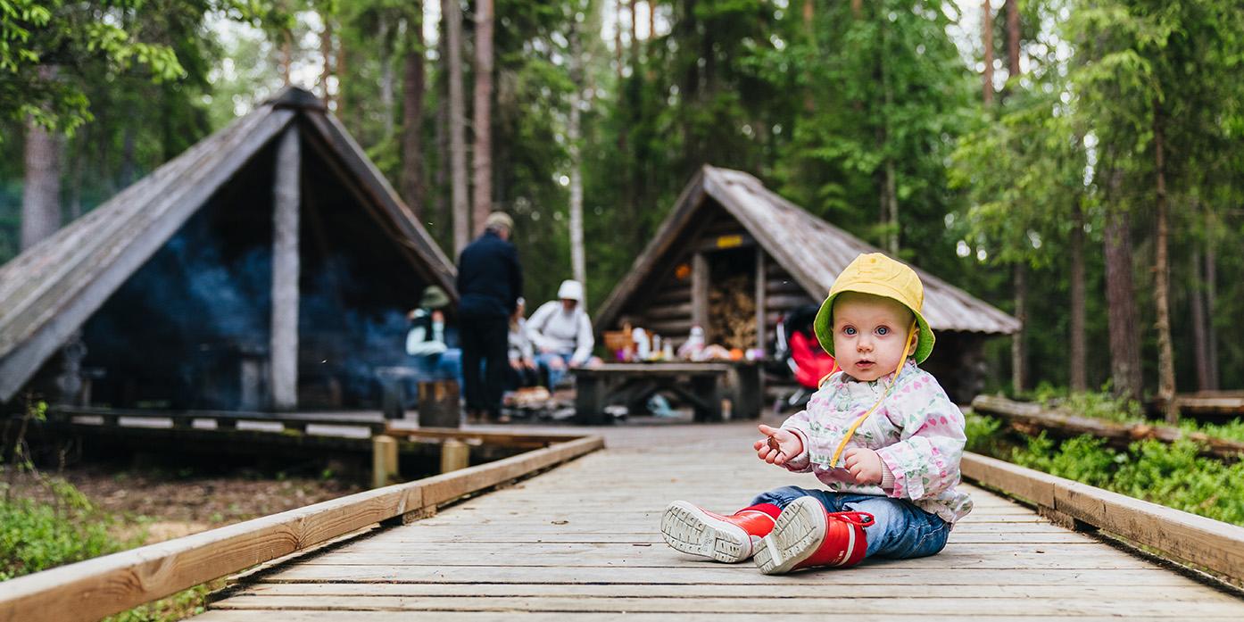 Lapsi istuu lankuista tehdyllä kulkutiellä, taustalla kaksi hirsilaavua ja eväiden syöjiä metsässä Napapiirin retkilyalueella Rovaniemellä.. Kuva Jaakko Posti.