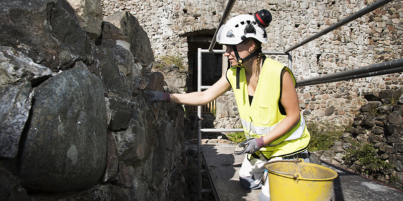Person reparing stone wall the medieval castle ruin of Raseborg. Photo by Elias Lahtinen.