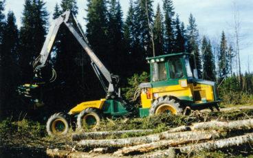 En skördare från 1980-talet arbetar på ett avverkat område.