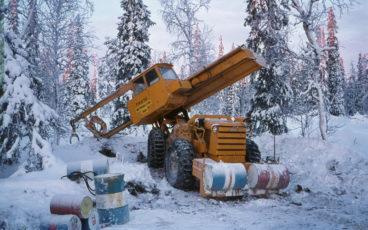 Traktorin päälle rakennettu prosessori poimii puita lumisessa metsässä. Etualalla öljytynnyreitä.