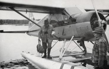 En man utrustad för vandring hoppar i land från ett pontonflygplan, svartvit bild.
