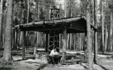 En man sitter vid ett bord vid en takförsedd eldplats i Petkeljärvi nationalpark, svartvit bild.