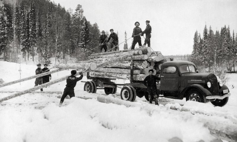 Män lastar timmerstockar på en bil vid en snöig skogsväg, svartvit bild.