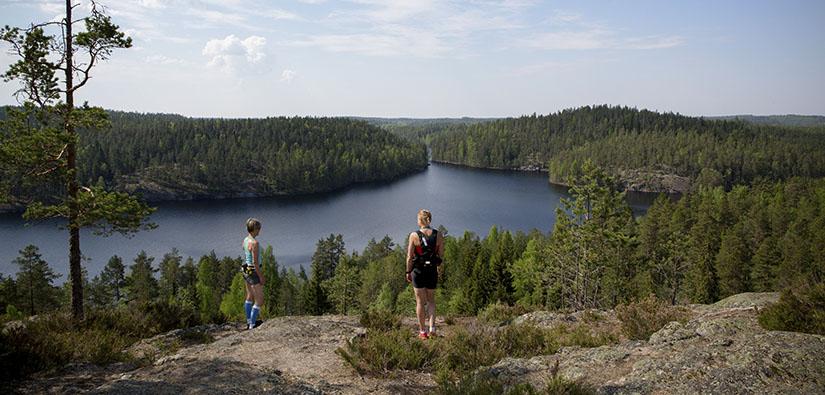 Kaksi juoksijaa katselee maisemia korkealla kalliolla. Alhaalla näkyy järvi ja metsää.
