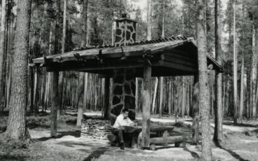 A man is sitting at the table at a campfire site in Petkeljärvi National Park, a black and white photo.