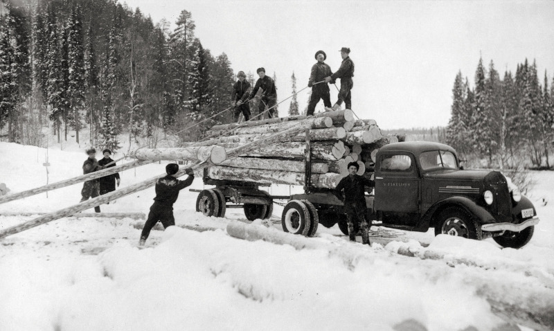 Men are loading logs into a truck by hand on a snowy forest road, a black and white image.