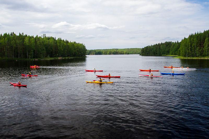 Ett tiotal kanoter paddlar på en lugn sjö. I bakgrunden öar.