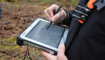 En av Forststyrelsens medarbetare använder ett geografiskt informationssystem på en bildskärmsenhet.