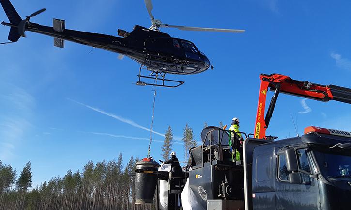 Flyggödsling med aska. En spridare som hänger från en helikopter fylls från ett upplag vid vägkanten.