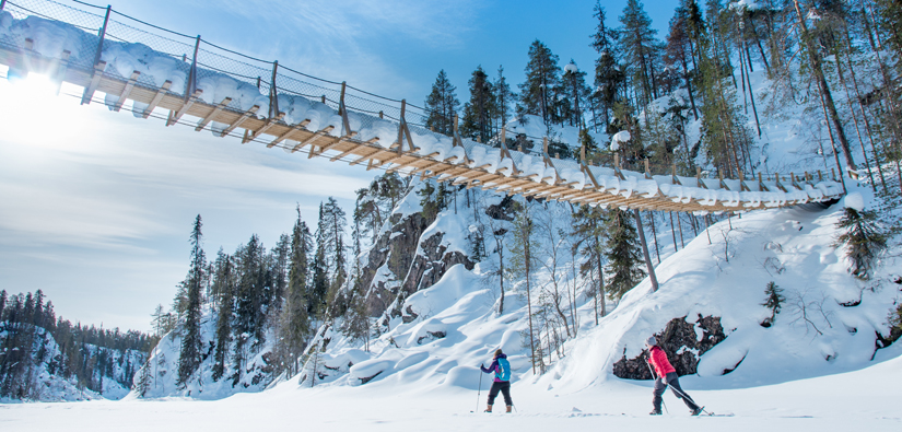 Two people skiing in sunny weather under a suspension bridge.