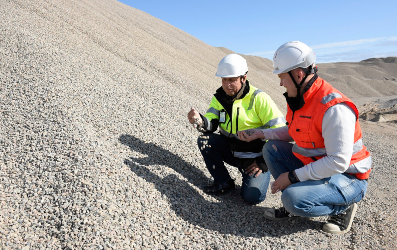 Two men dressed in work clothes look at the gravel on a gravel pit.
