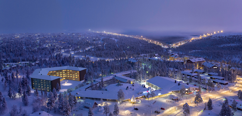 An aerial photograph of Lake Saariselkä, with an illustration of a big hotel. Ski slopes can be seen in the background.