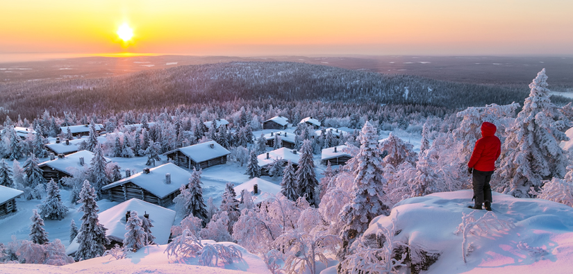 A man looking down from a snowy cliff towards a cottage village and a sunset.
