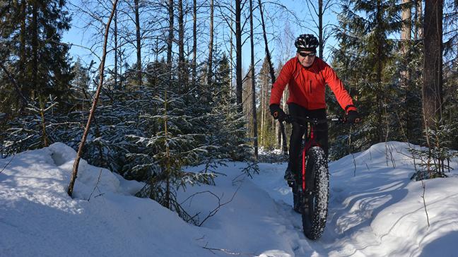 En terrängcyklist åker fatbike längs en snöig stig genom en mångbruksskog i vinterskrud.