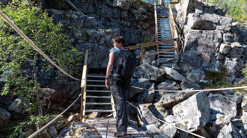 Retkeilijä seisoo kallioisessa laaksossa, edessä ylös rinteeseen nousevat portaat.