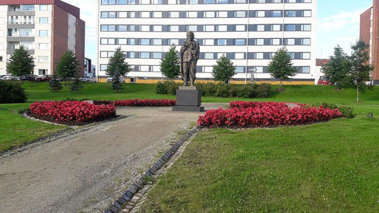Eino Leinon patsas kukkaistutusten keskellä. Taustalla kerrostaloja.
